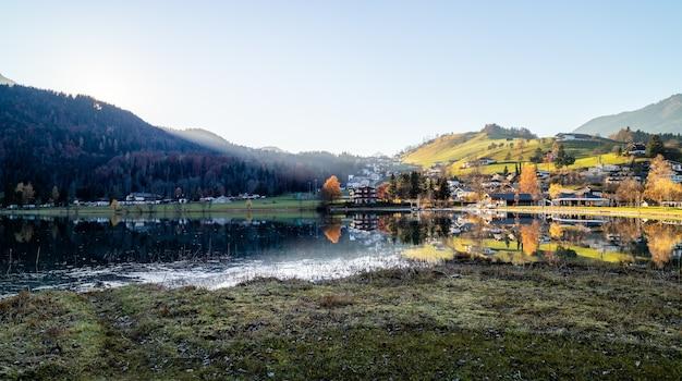Platteland panoramisch landschap met traditionele gebouwen en huizen, silhouet van bergen aan de oever van het meer, oostenrijk.
