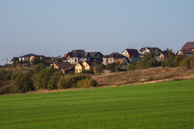 Plattelands leven. een dorp op een heuvel. een groen lenteveld voor een modern dorp op een heuvel tegen een helderblauwe lucht. landbouwgrond.