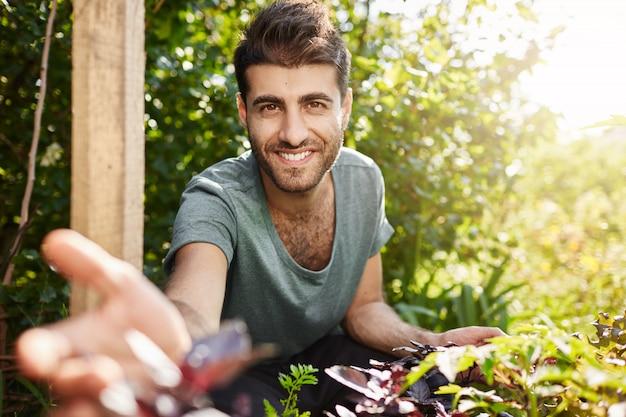 Plattelandsleven, naature. close-up buiten portret van jonge aantrekkelijke bebaarde blanke man in blauw t-shirt glimlachen