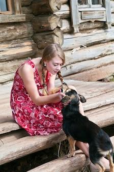 Plattelandsmeisje speelt met een hond