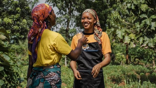 Plattelandsvrouwen die in het veld bespreken