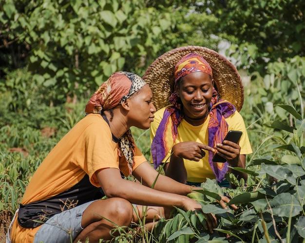 Plattelandsvrouwen die samen een telefoon doorbladeren