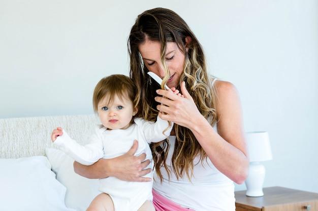 Playfu baby probeert het haar van een brunette vrouw te kammen