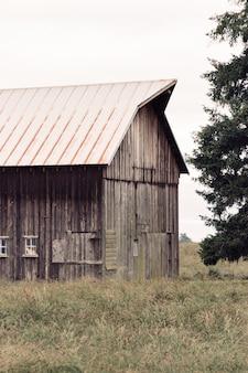 Pld houten schuur gebouwd in een groot veld naast een boom