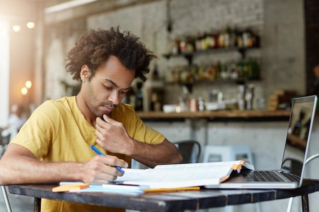 Plechtige donkerhuidige afro-amerikaanse student op zijn werkplek die in zijn exemplaarboek kijkt en notities schrijft die zich voorbereiden op eindexamens op de universiteit. geconcentreerde knappe jongen die tijdens pauze in café werkt