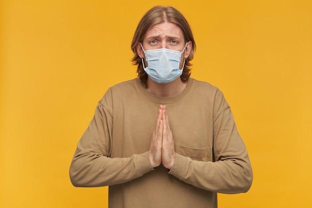 Pleiten mannelijke, knappe bebaarde man met blond kapsel. beige trui en medisch beschermend gezichtsmasker dragen. houdt handpalmen vast in een gebed. geïsoleerd over gele muur