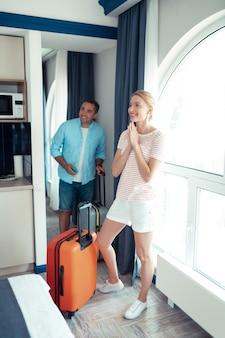 Plek om te ontspannen. vrolijke man en vrouw zijn onder de indruk van hun hotelkamer die met hun reiskoffers bij het grote raam staat.