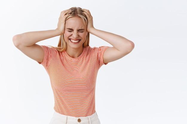 Plezier, geluk en welzijn concept. aantrekkelijke blonde moderne vrouw in stijlvol gestreept t-shirt met tatoeages, hand in hand op het hoofd ontspannen vrolijke pose, glimlachend en hardop lachen