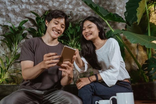 Plezier hebben bij coffeeshop met vriendin en het gebruik van mobiele telefoon, tienerpaar concept