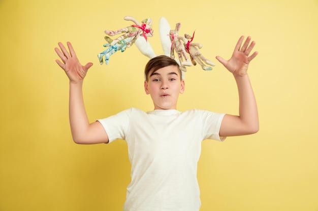 Plezier hebben. decoreren. blanke jongen als paashaas op gele studioachtergrond. gelukkige pasen-groeten.