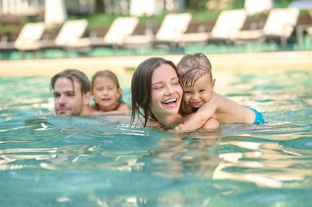 Plezier hebben. een jong gezin dat plezier heeft in een zwembad en er leuk uitziet