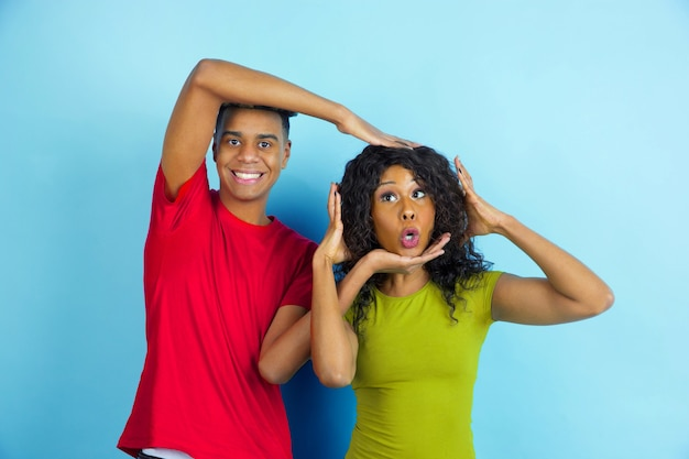 Plezier hebben en gremaces. jonge emotionele afro-amerikaanse man en vrouw in vrijetijdskleding die zich voordeed op blauwe achtergrond. mooi paar. concept van menselijke emoties, gezichtsuitdrukkingen, relaties, advertentie.
