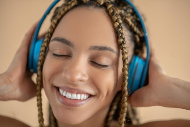 Plezier hebben. glimlachend jonge african american vrouw in blauwe koptelefoon, luisteren naar muziek met gesloten ogen