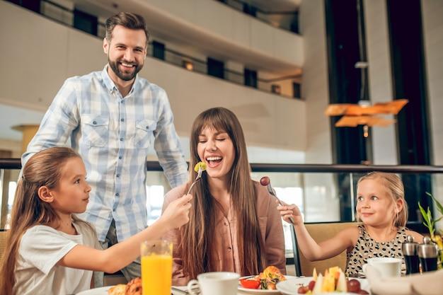 Plezier hebben. glimlachende familie aan de tafel zitten en plezier maken