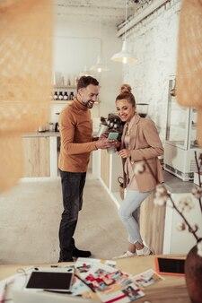 Plezier hebben. glimlachende knappe man die grappige video op zijn smartphone laat zien aan zijn mooie collega.