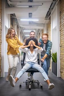 Plezier hebben. groep jonge mensen die de stoel in de bureaucorridor berijden na een mooie dag