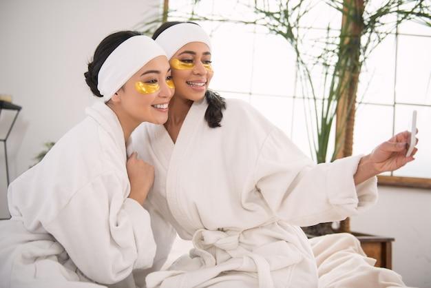 Plezier hebben. hay was opgetogen over vrouwen die naar de camera van hun smartphone lachten terwijl ze samen plezier maakten in de spa