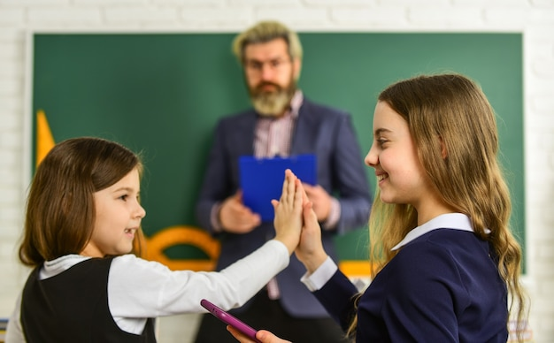 Plezier hebben. kleine meisjes kinderen op school. terug naar school. leraar en leerlingen werken samen aan bureau op de basisschool. creativiteit onthullen en ontwikkelen. leraar werken met creatieve kinderen.