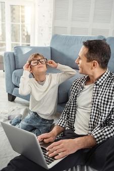 Plezier hebben. knappe waakzame blonde jongen die glimlacht en een grote bril draagt en zijn vader lacht en zij zitten op de vloer