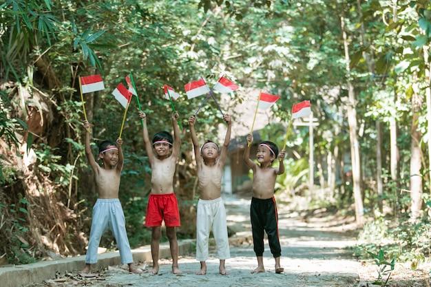 Plezier hebben met een groep kinderen die zonder kleren staan terwijl ze de rode en witte vlag vasthouden