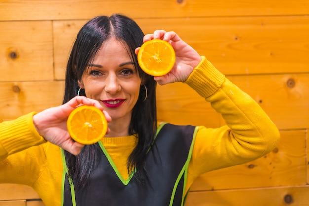 Plezier hebben met sinaasappels in de hand van een donkerbruin kaukasisch fruitmeisje, werkzaam in een groenteboer