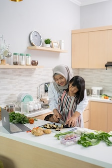 Plezier hebben moslimvrouw met hijab en kind samen diner voorbereiden