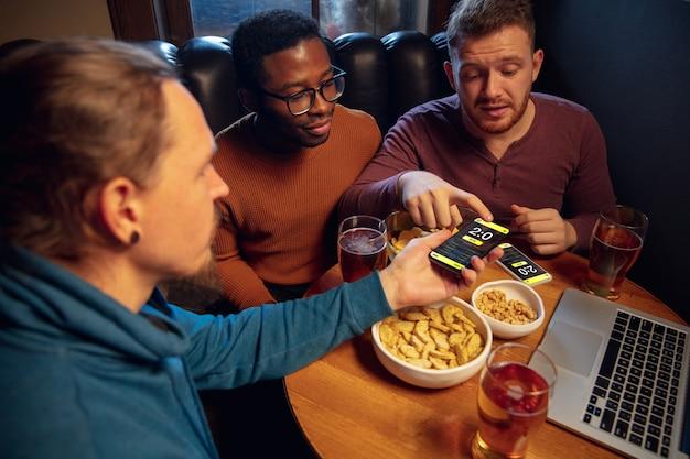 Plezier hebben. opgewonden fans in bar met bier en mobiele app om te wedden, scoren op hun apparaten. scherm met wedstrijdresultaten, emotionele vrienden juichen. gokken, sport, financiën, modern techn-concept.