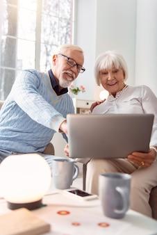 Plezier hebben. vrolijke senior paar zitten in de woonkamer en kijken naar een grappige video op hun laptop terwijl de man naar zijn favoriete moment wijst