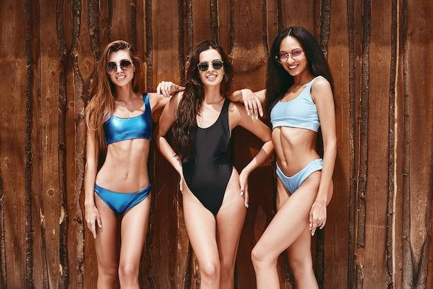 Plezier in de zon vrolijke meisjes in zwemkleding poseren geïsoleerd over houten achtergrond vooraanzicht