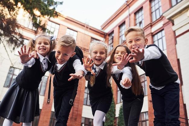Plezier maken en elkaar omhelzen. groep kinderen in schooluniform dat buiten samen is in de buurt van het onderwijsgebouw.