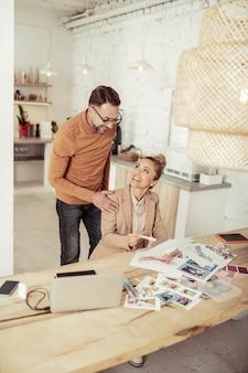 Plezier op het werk. twee vrolijke collega-ontwerpers lachen om een grap die bij de tafel zit en staat.