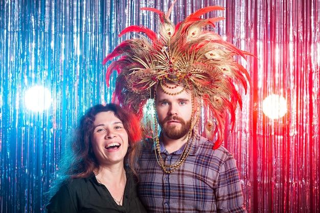 Plezier, vakantie en vreemde mensen concept - vrolijke jonge vrouw en grappige man in carnaval hoed op zoek