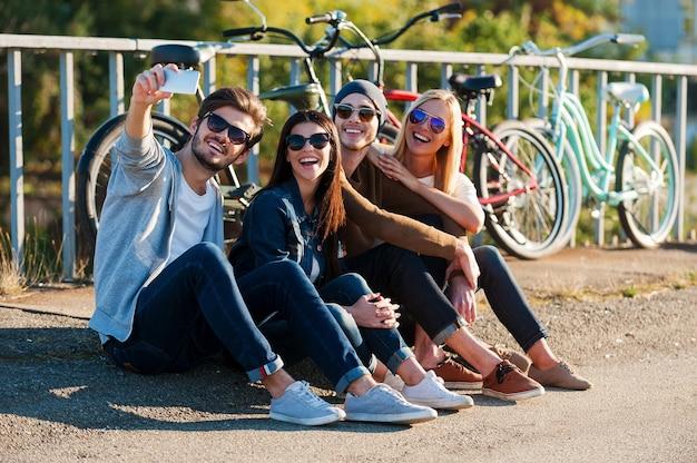 Plezier vastleggen. groep jonge lachende mensen die zich aan elkaar hechten en selfie maken via een smartphone terwijl ze buiten zitten samen met fietsen op de achtergrond