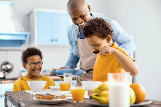 Plezier voor de ogen. vrolijke jonge vader die zijn kleine kinderen bekijkt die granen eten en liefdevol glimlachen terwijl hij een koekenpan met een omelet brengt