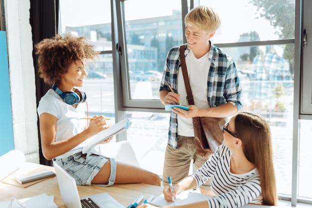 Plezierig onderwijs. vrolijke glimlachende jonge studenten die aantekeningen maken en samen studeren terwijl ze een pauze hebben