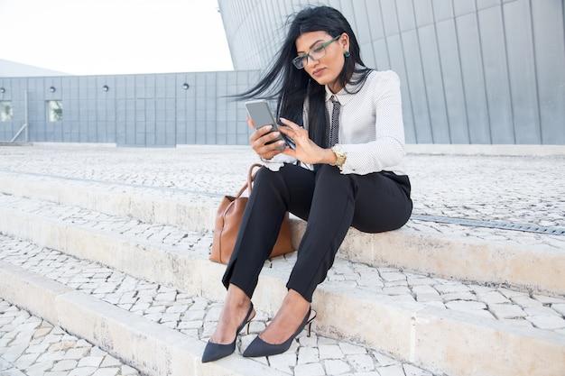 Plezierige zakenvrouw die op sms reageert op telefoon