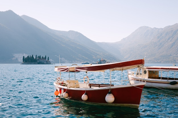 Pleziervaartuigen met zonnescherm op het water van de baai van kotor bij de bergen.