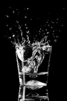Plons water in een glas, spatten verspreiden zich in verschillende richtingen. element concept water