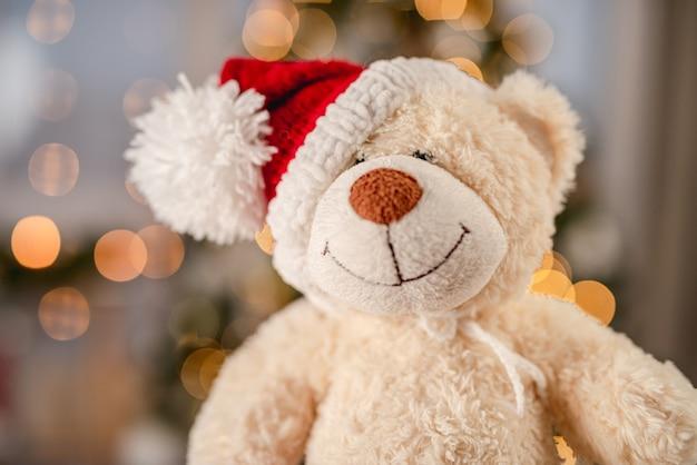 Pluche teddybeer speelgoed in kerstmuts op de achtergrond van huis nieuwe jaarverlichting