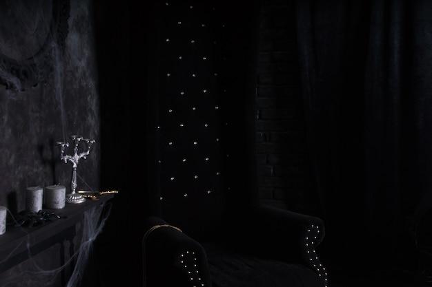 Pluche zwarte stoel met hoge rugleuning en kandelaars met spinnenwebben in angstaanjagende halloween-spookhuisomgeving