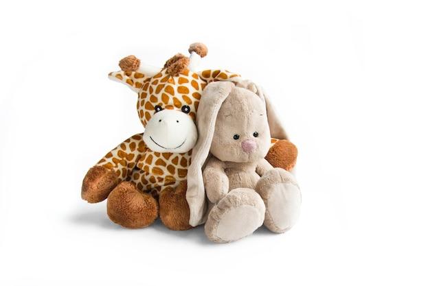 Pluchen speelgoed witte en bruine giraf en grijs konijn geïsoleerd op een witte achtergrond