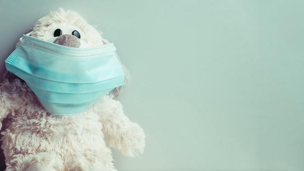 Pluchestuk speelgoed met medisch masker op lichtgroen