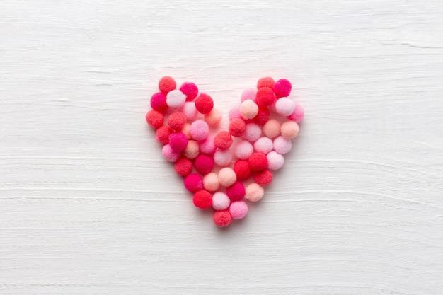 Pluizig hart als symbool van liefde op witte houten achtergrond voor moederdag of st valentine-dag