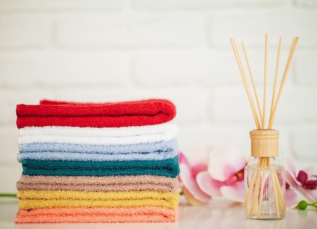 Pluizige badhanddoeken op lichte houten tafel met aromastokken