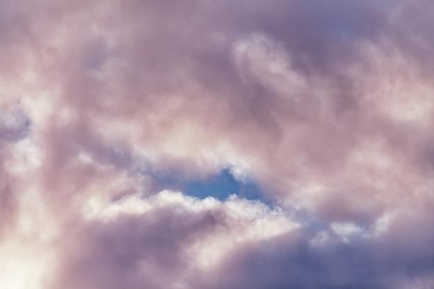 Pluizige cumuluswolken in mooie paarse en roze kleur, azuurblauwe bewolkte hemel