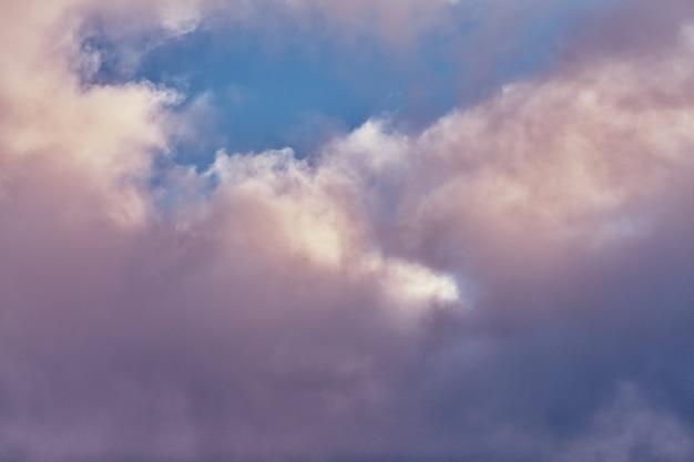 Pluizige cumuluswolken in prachtige paarse en roze kleur, azuurblauwe bewolkte hemel. wolkenlandschap.