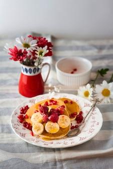 Pluizige pannenkoeken met bananen en frambozen op plaat