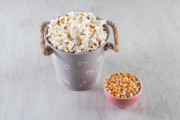 Pluizige popcorn en rauwe maïskorrels op stenen achtergrond.