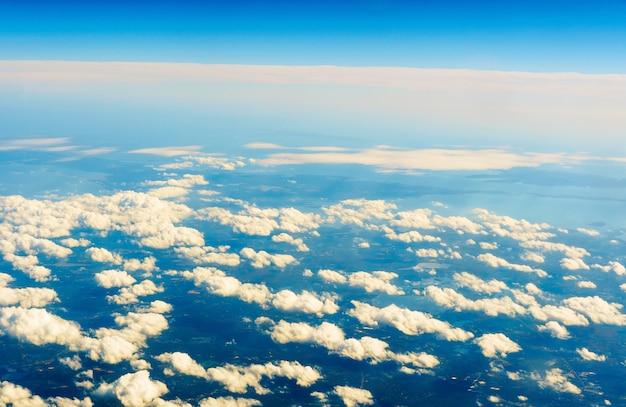 Pluizige witte wolken en blauwe lucht gezien vanuit het vliegtuig. vlucht wolk lucht