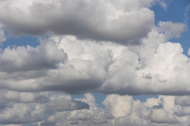 Pluizige wolken en blauwe hemelachtergrond